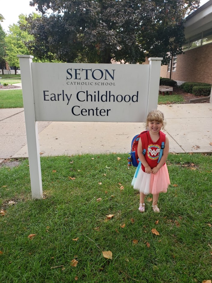 Scout in front of her preschool sign